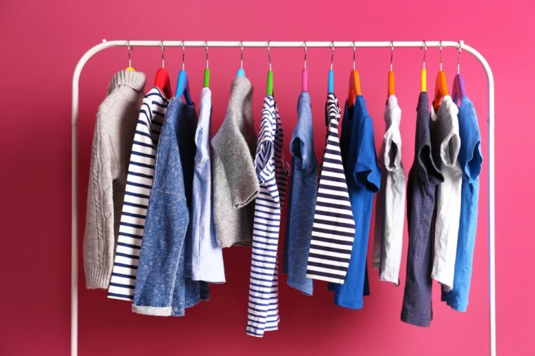 Hangers with colourful clothes on pink background