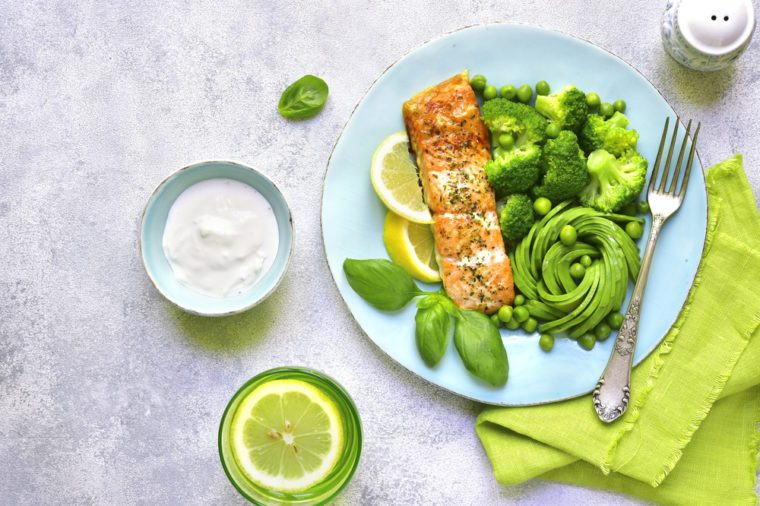 Grilled salmon garnished with green vegetables on a blue plate on light slate,stone or concrete background.Top view.