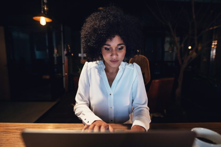 Young black businesswoman working late on laptop in office. Beautiful female entrepreneur using laptop while sitting at a table.