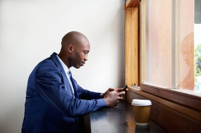 Side portrait of black businessman sitting in a cafe sending text message on cell phone