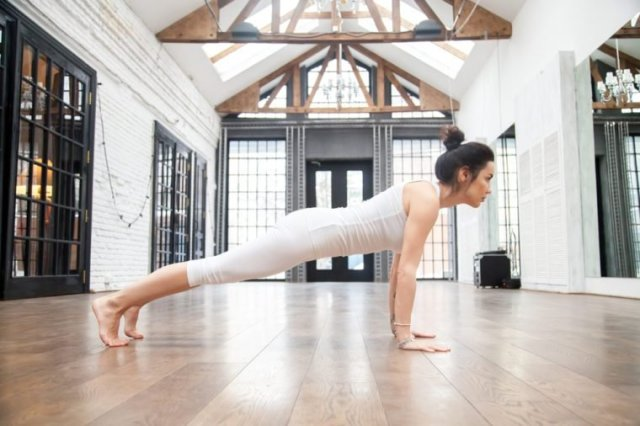 Full length side view portrait of attractive young woman working out in luxury fitness center, doing push ups, press ups, yoga or pilates exercise without mat on wooden floor, standing in plank pose