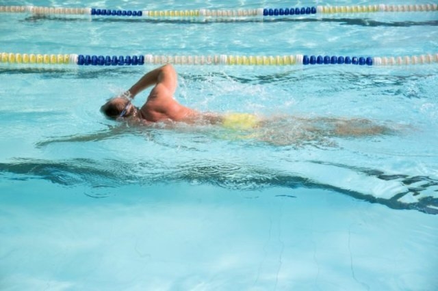 Motion of fit and healthy senior man swimming freestyle training in the pool. Happy pensioner enjoying sportive lifestyle. Active retirement concept.