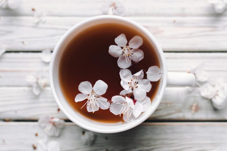 Cup of tea and spring apricot blossom on a white wooden background. Overhead view. Rustic.