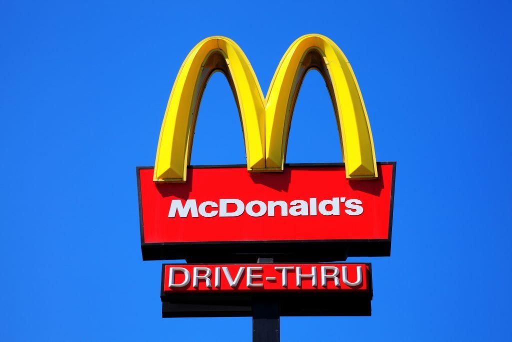 London, United Kingdom, May 27, 2012 : McDonald's yellow and red drive-thru logo advertising sign placed on a pole with a clear blue sky