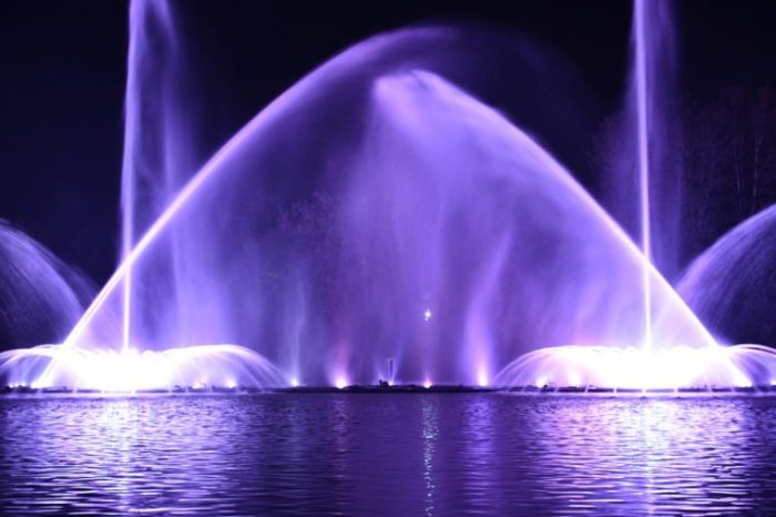 """Musical fountain with laser animations. Night laser fountain show, on the Roshen embankment, the Ukrainian city of Vinnitsa.Musical fountain """"Roshen"""" in Vinnitsa, Ukraine.Evening show Roshen fountain."""