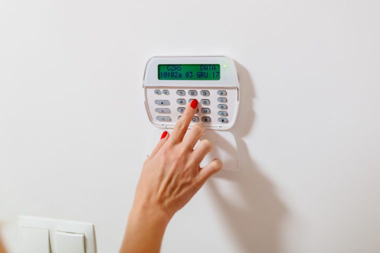 Woman entering security pin password on home security alarm keypad