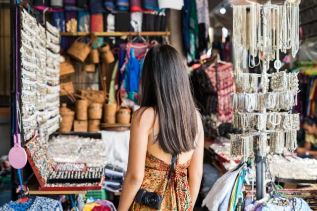 Young woman traveler looking for some souvenir at ubud market in bali