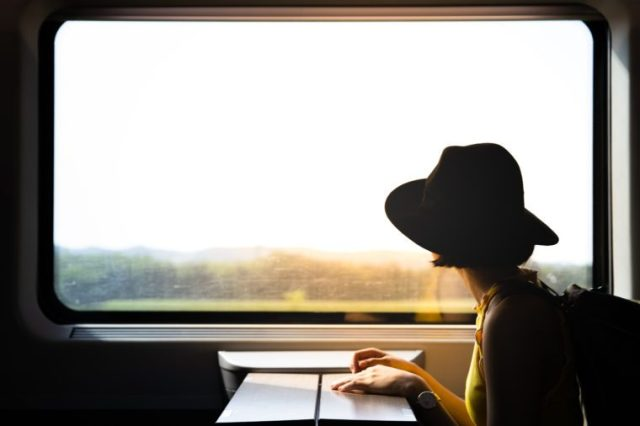 A beautiful hipster asian woman travelling on the train. Sitting on the black leather cozy comfort seat in the business class boky of the train in Europe. Tourist travel concept.