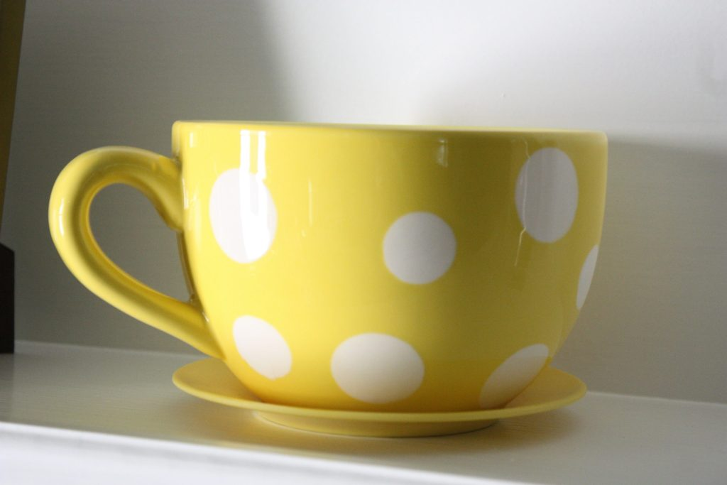 over sized yellow coffee cup with white polka dots