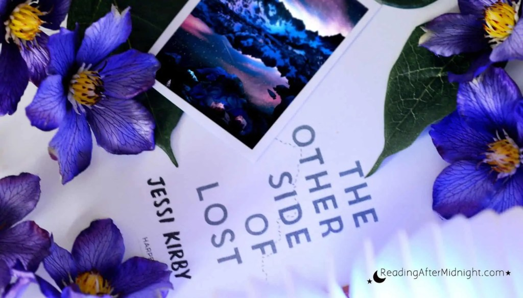The cover of The Other Side of Lost by Jessi Kirby with purple flowers placed on top