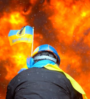 Protester wearing Ukraine state flag colors facing the massive fire set by protesters to prevent internal forces from crossing the barricade line. Kiev, Ukraine. 2014. Used via Wikimedia Commons.
