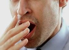 man stifling a yawn