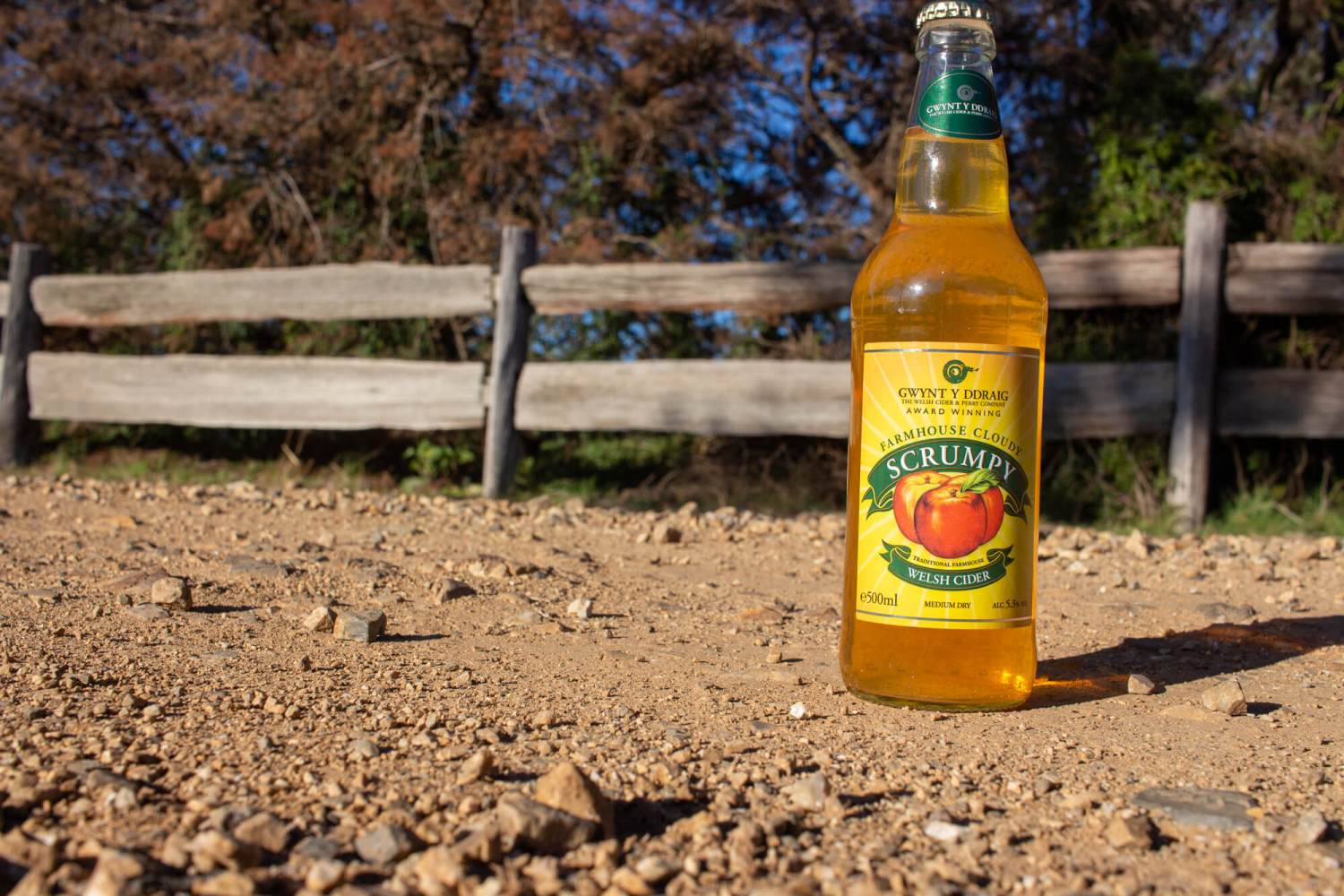 Bottle of Gwynt Y Ddraig Farmhouse Cloudy Scrumpy on a dusty road