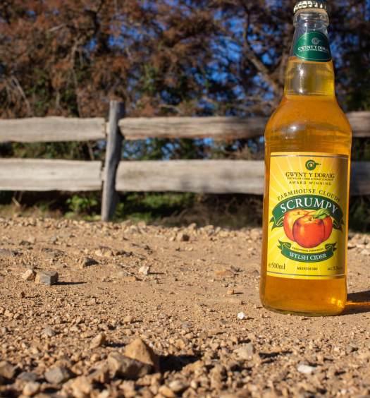 Bottle of Gwynt Y Ddraig Farmhouse Cloudy Scrumpy on a dusty road