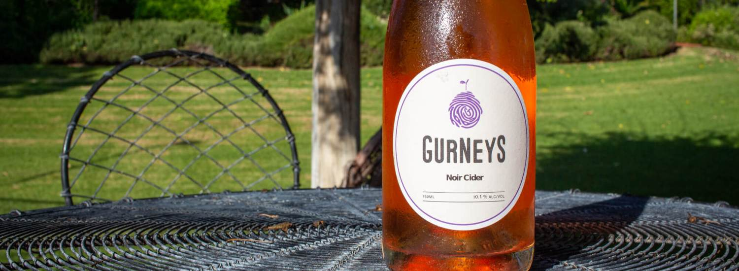 A bottle of Gurney's Noir Cider on a garden table