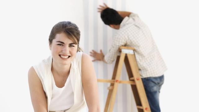 Algemeen beeld van de renovatie van het huisdecor. Vrouw die lijm op behang aanbrengt terwijl man op ladder staat en behang aan de muur plakt.