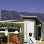 An engineer shows a homeowner a roof with solar panels for a house off the grid