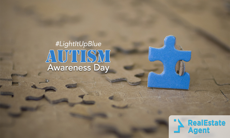 Blue puzzle piece in the middle of several cardboard puzzle pieces with #Lightitupblue Autism Awareness day written on the side