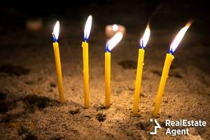 Long Yellow candles burning in a sand at the Romanian night