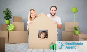 Mom, dad and daughter behind a cardboard house on front of several boxes ready for a home relocation