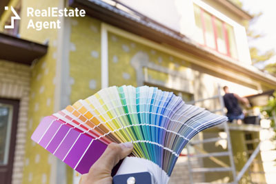 man holding color palette samples for exterior painting
