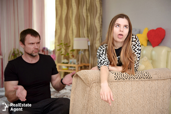 teenage girl making a funny face and acting rebellious while her father is having a talk with her