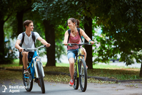 boy and girl riding bicycle and smiling to each other, teenager love