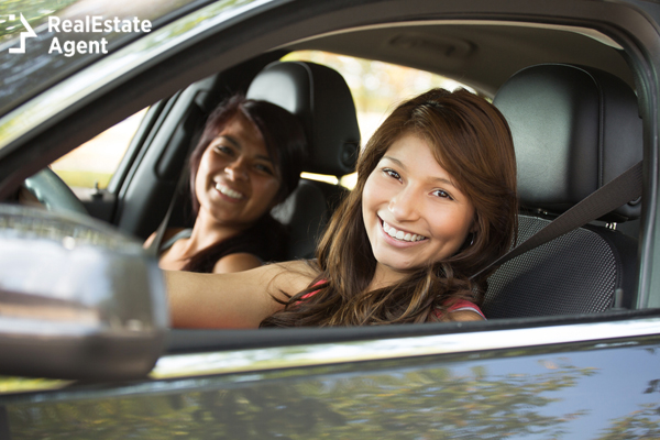 teenage girl driving while her mom sits in the passenger seat