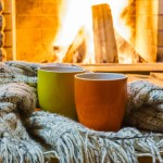 Two mugs wrapped in scarf in front of fireplace