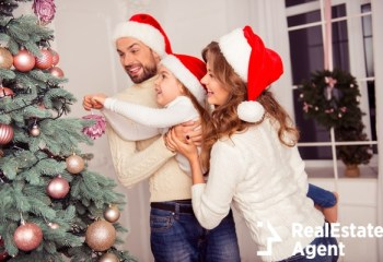mom dad little daughter decorating christmas tree
