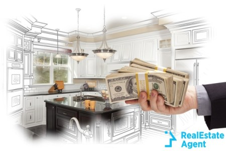 Disembodied hand holding cash over home design