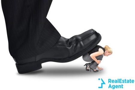 Big corporate foot is stepping on a small woman employee
