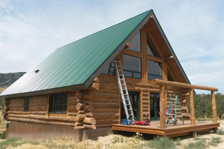 Cleaning windows on a log cabin