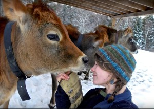 Caitlin Frame nuzzles a cow in her winter hat outside at the Milkhouse dairy farm and creamery