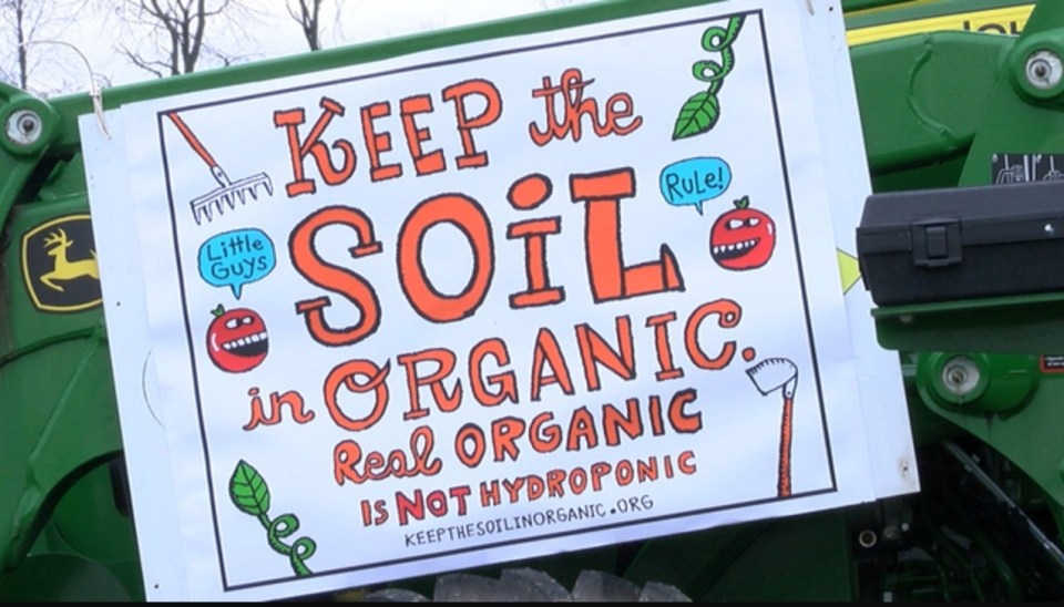 A Keep the Soil in Organic sign is posted to a tractor at an organic farm rally planned by Vermont's Davey Miskell