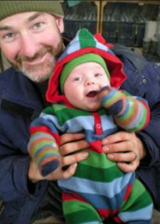 Gregg Stevens holds a baby - probably one of his