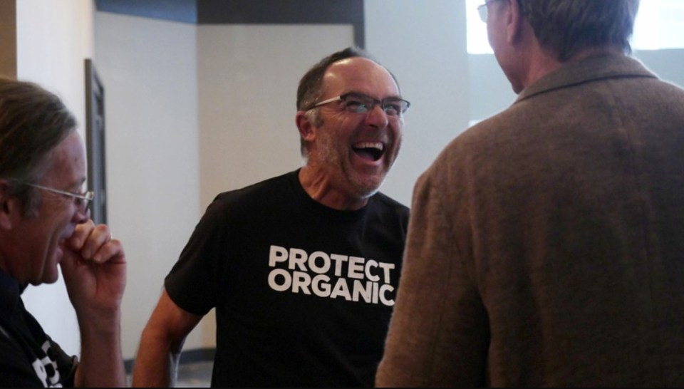 Organic farmer Mike Brownback is all smiles in his Protect Organic t shirt in Jacksonville where he testified to the National Organic Standards Board