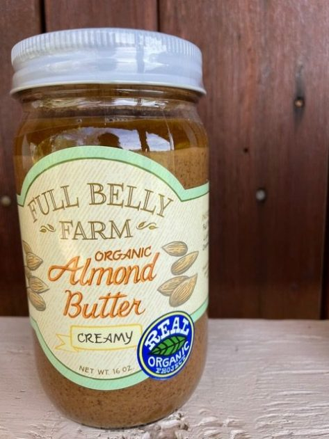 A glass jar filled with almond butter and a logo reading Full Belly Farm Almond Butter