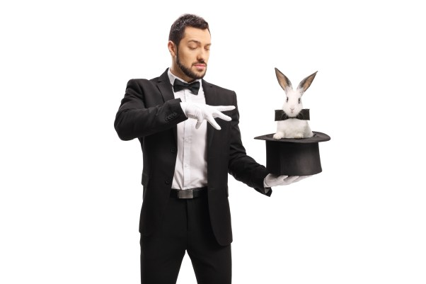 A magician in a tuxedo holds a top hat with a rabbit