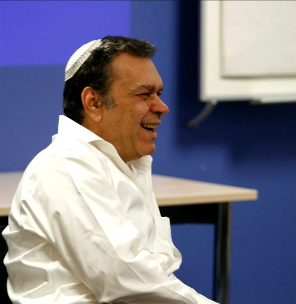 Thinker and author Eliyahu Goldratt laughs while wearing a white shirt against a blue background