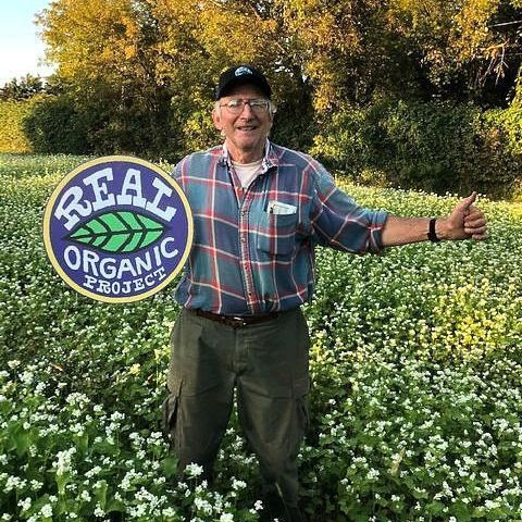 A smiling farmer stands in a field of cover crop with white flowers. He holds a Real Organic Project logo sign and has his other arm outstretched.