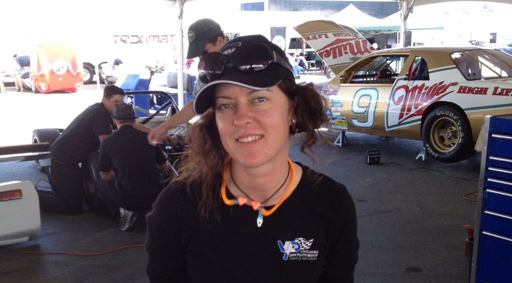 woman sitting on a stack of race wheels, wearing ear protection and safety glasses while in the background you can see a gold colored Nascar car jacked up with the hood open