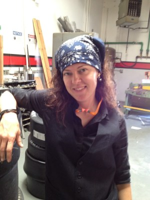 woman wearing a blue bandanna, dark long sleeved button down shirt under a pinstripe vest and ear protection hanging around her neck standing in the middle of a workshop