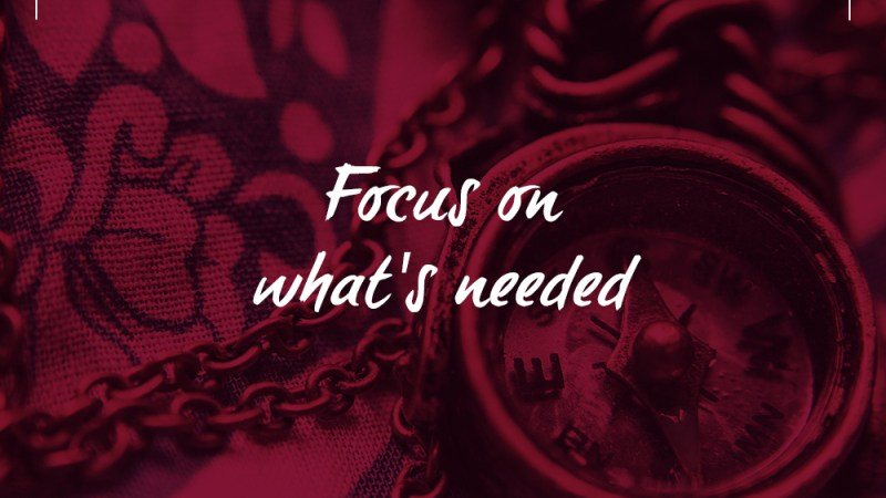 red photo of a compass and its chain draped across a blanket with the words Focus on what's needed written across the middle and the Real To Ideal branding decor.