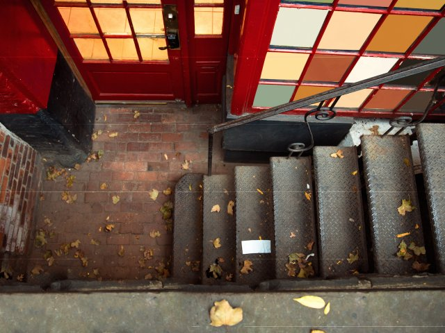 Exterior steps lead to underground basement apartment on city street