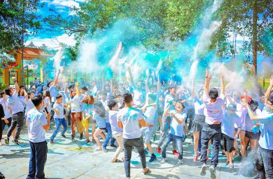 group of teens playing with color powder