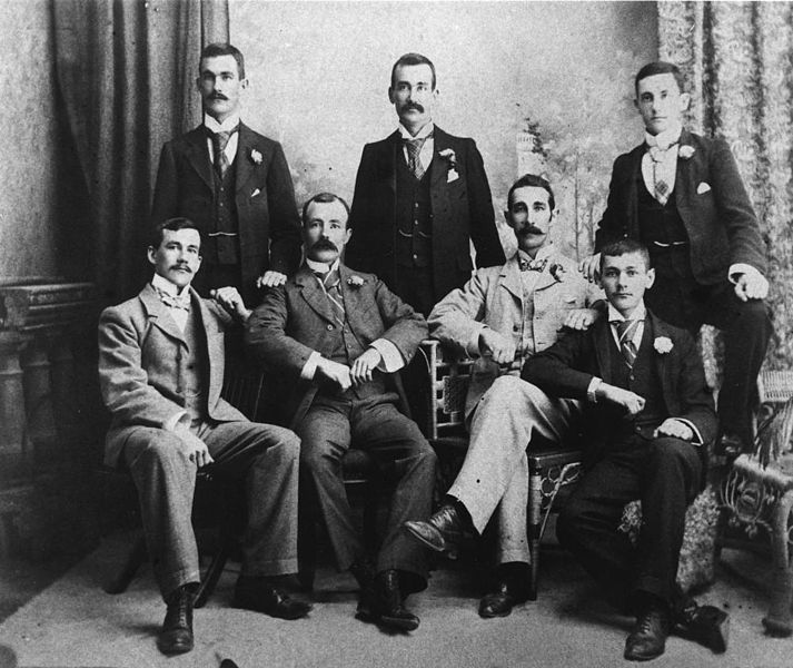 An old photo of men in suits posing for a picture in the late 1800s