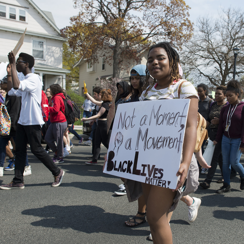 A woman on a black lives matter protest with a banner that says 'not a moment, a movement. Black lives matter'
