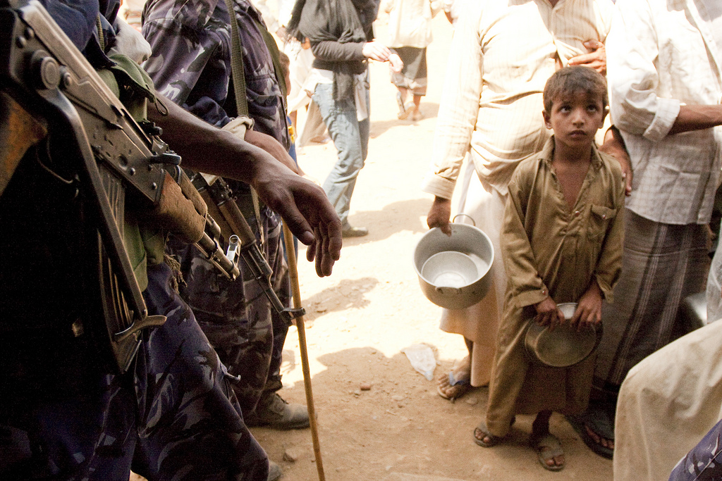 A picture of a boy waiting in a food line who recently fled the Yemen capital