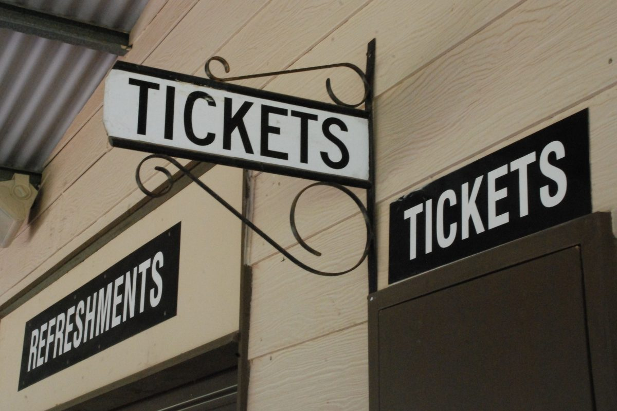 """a wooden building that has signs for """"Refreshments"""" and """"Tickets"""" above two doors."""